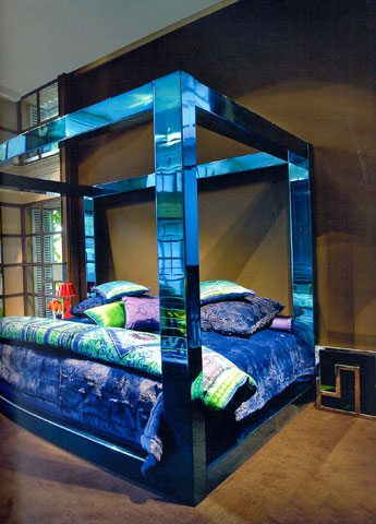 Conforter by Versace: The precious texture of dark blue mitigates the severity of the geometric lined of the bed lit up by metal reflections